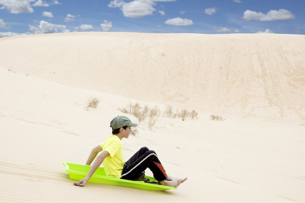 Child on a sled pulls off the sandy mountains. Monahans Sandhills State Park, Texas