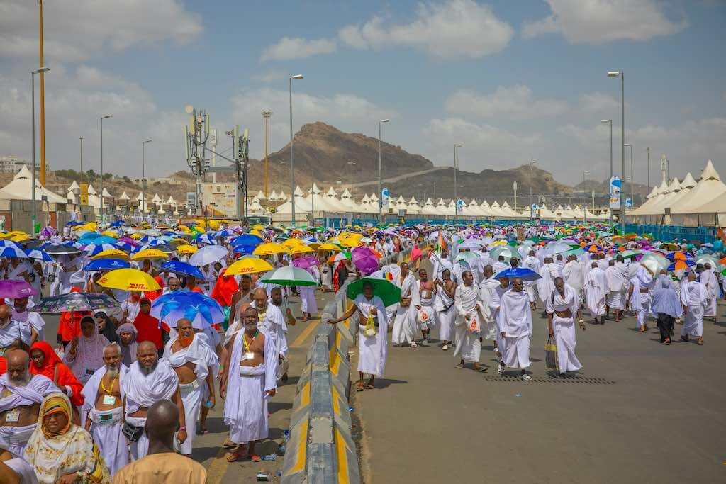Hajj pilgrims walking down the road, Mina, Makkah, Saudi Arabia - by Leo Morgan / Shutterstock.com